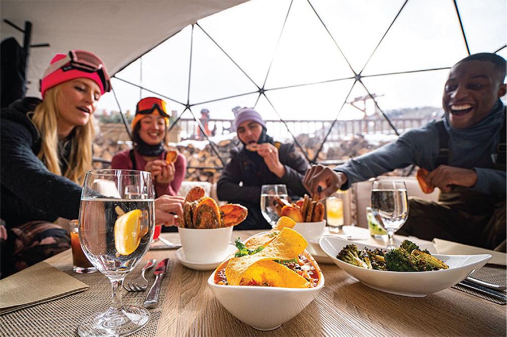 Friends Sharing food inside Vail Snow Cabana